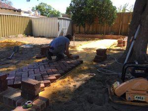 landscaper laying brick pathway in garden